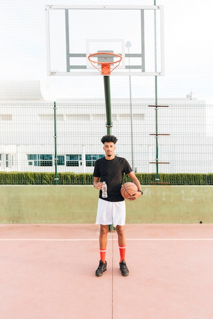 Ethnic young man holding basketball at court Free Photo