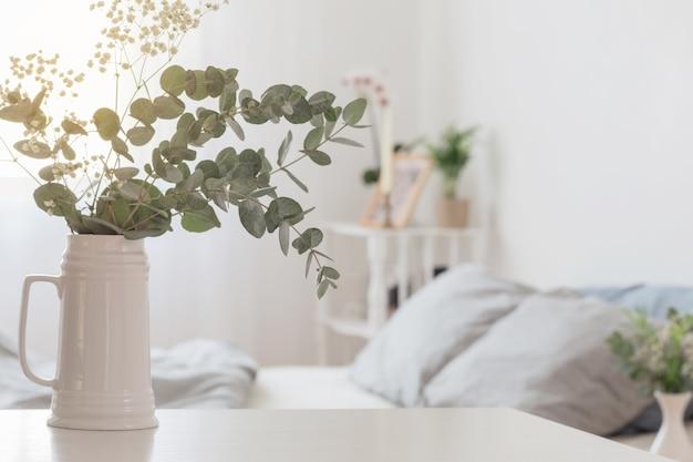 Эвкалипт и гипсофила в кувшине в белой спальне Premium Фотографии