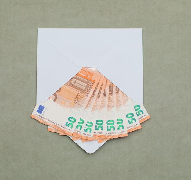 Евро счета в конверте на зеленовато-серый стол. Бесплатные Фотографии