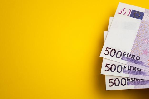 Euro cash, banknotes on the yellow table Premium Photo