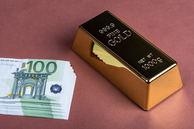 Euro cash and gold bar on a brown surface. Premium Photo