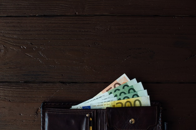 Euro cash open brown male wallet with euro banknotes on wooden background 8353 6553