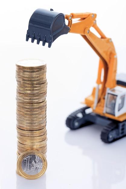 Monete dei soldi di euro e scavatrice isolati su spazio bianco Foto Gratuite