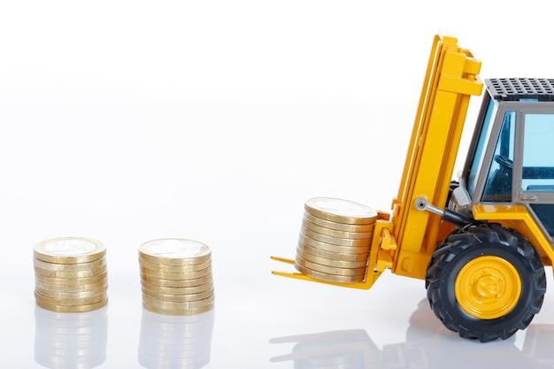 Monete dei soldi dell'euro e carrello elevatore isolati su spazio bianco Foto Gratuite