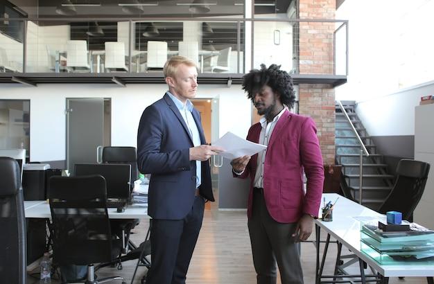 비즈니스 회의 중에 계약을 논의하는 유럽 및 아프리카 계 미국인 비즈니스 파트너 무료 사진