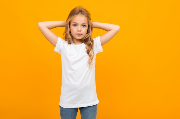 European attractive girl in a white t-shirt with a mockup on a yellow Premium Photo