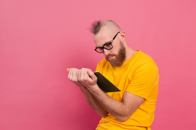 L'uomo adulto barbuto europeo in vetri ha letto il libro isolato sul rosa Foto Gratuite