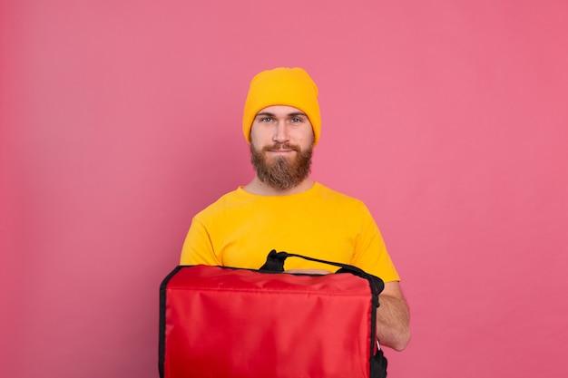 Uomo di consegna barbuto europeo con scatola con cibo in rosa Foto Gratuite