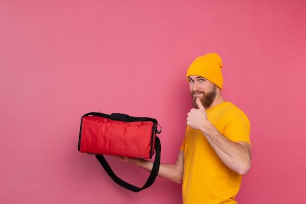 Европейский бородатый курьер с коробкой с едой улыбается и показывает палец вверх на розовом Бесплатные Фотографии