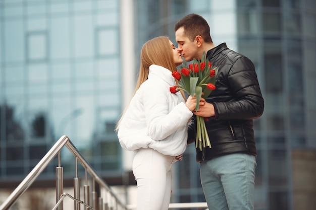 Европейская пара стоит вместе с цветами Бесплатные Фотографии