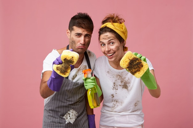 European couple wiping out all dust with sponges and detergent Free Photo