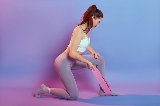 Европейская темноволосая, одетая в спортивный белый короткий топ и спортивные леггинсы, делает упражнения для трицепсов с резиновыми резинками для спортивного фитнеса, выделенными на цветном фоне, смотрит вниз, стоит на одном колене. Бесплатные Фотографии