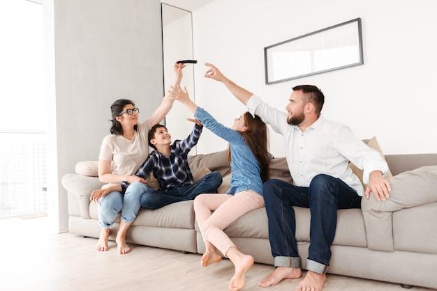 Европейская семья с сыном и дочерью сидят на диване вместе в гостиной дома и пытаются отобрать смартфон у женщины Premium Фотографии