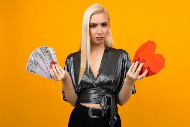 Европейская девушка с большим количеством денег и в форме сердца на желтой стене Premium Фотографии