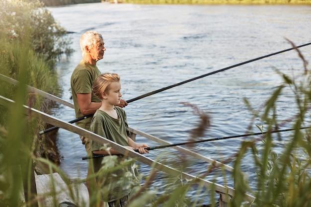 야외에서 호수 또는 강에서 낚시하는 아들과 함께 유럽의 회색 머리 성숙한 아버지, 손에 낚싯대를 들고 물 근처에 서서 캐주얼하게 옷을 입고 취미와 자연을 즐기십시오. 무료 사진