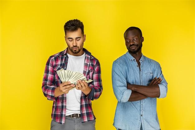 Европейский парень считает деньги, а афроамериканец смотрит на него Бесплатные Фотографии