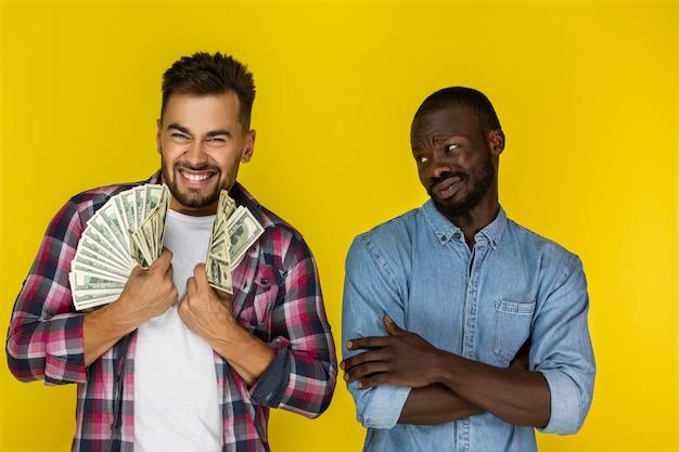 Un ragazzo europeo con una grossa somma di denaro in entrambe le mani sorride frettolosamente e un ragazzo afroamericano non ha niente che lo guarda in abiti informali Foto Gratuite