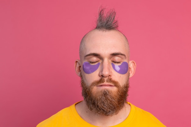 노란색 티셔츠와 분홍색에 보라색 눈 패치 마스크에 유럽의 잘 생긴 수염 난된 남자 무료 사진