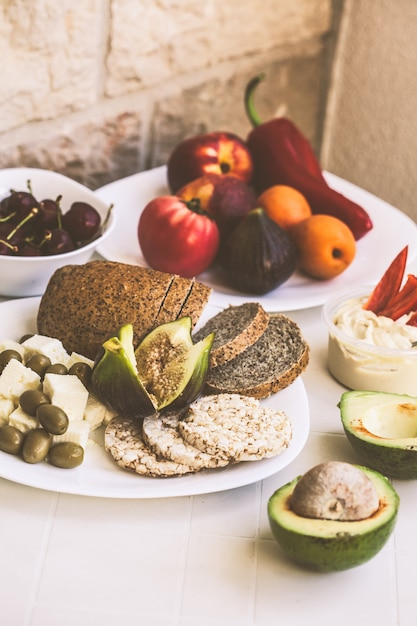 European healthy vegetarian food on a white table on the balcony Premium Photo