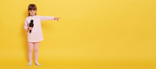 마이크가있는 유럽 소녀는 마이크를 잡고 카메라를 바라보고 광고 또는 홍보를 위해 빈 공간에 검지 손가락을 옆으로 가리 킵니다. 매력적인 보컬리스트가 노란색 벽에 무언가를 제시합니다. 무료 사진