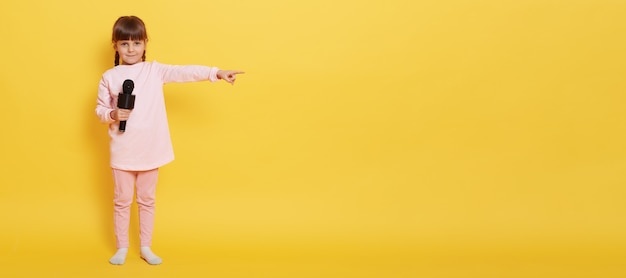 European little girl with microphone looks at camera while holding mic, points index finger aside at empty space for advertisement or promotion, charming vocalist presenting something at yellow wall. Free Photo