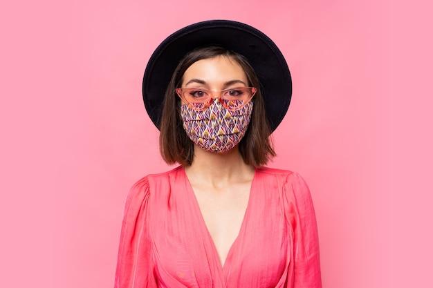 유럽 모델은 세련된 얼굴 마스크를 보호합니다. 검은 모자와 선글라스를 쓰고. 분홍색 벽 위에 포즈 무료 사진