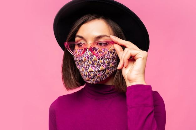 유럽 모델은 세련된 얼굴 마스크를 보호합니다. 검은 모자와 선글라스를 착용. 무료 사진