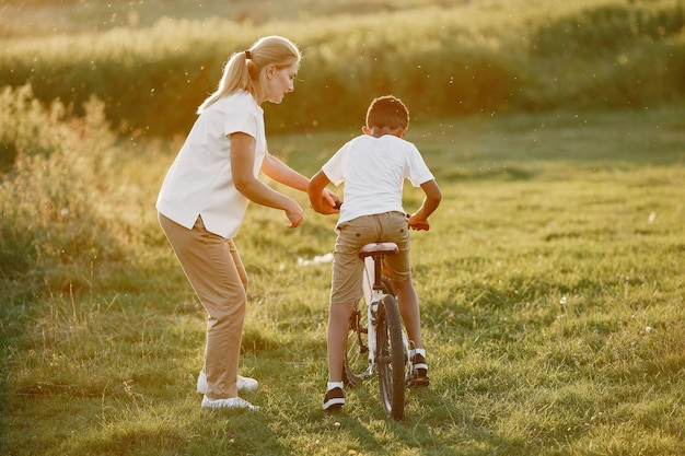 European mother and african son. family in a summer park. kid with bicycle. Free Photo
