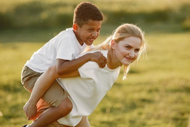 ヨーロッパ人の母親とアフリカ人の息子。サマーパークの家族。 無料写真