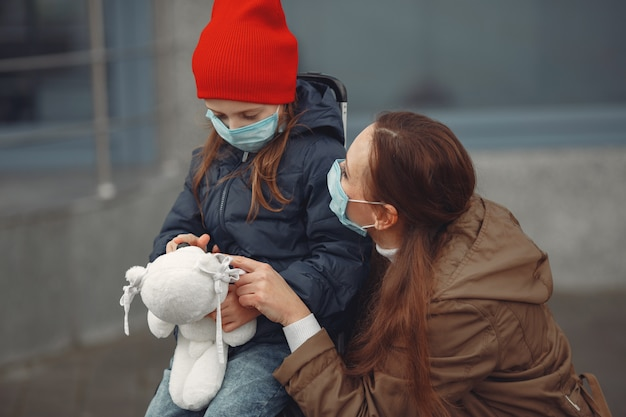 A european mother in a respirator with her daughter are standing near a building.the parent is teaching her child how to wear protective mask to save herself from virus Free Photo