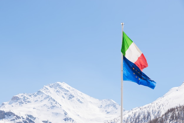 European union and italian flag blowing in the wind on the alps Premium Photo