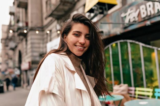 幸せな笑顔と黒髪のヨーロッパの女性がカメラに微笑んで幸せな感情で歩く 無料写真