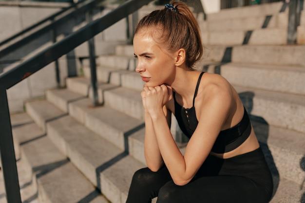 コンクリートの階段に座っているスポーツ黒の制服を着たヨーロッパの若い女性。 無料写真