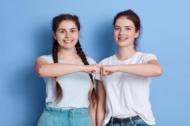 ヨーロッパの若い女性はお互いに拳バンプを与える Premium写真