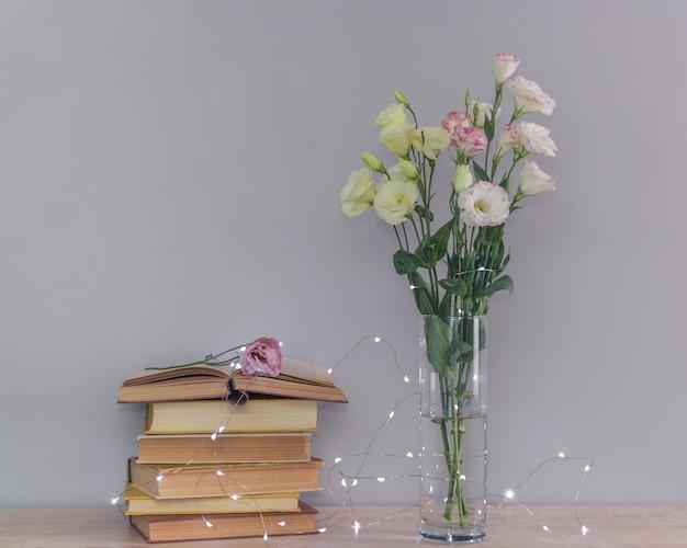 ユーストマの花の花束、古いヴィンテージの本と花輪のライトのスタック。コンセプトを読んでリラックスしてください。 Premium写真