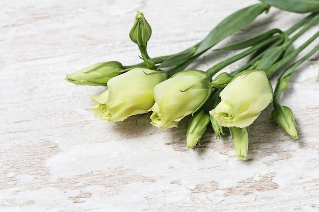 Eustoma свежих белых цветков на деревянном столе с космосом экземпляра. молодые нежные цветочные бутоны. Premium Фотографии