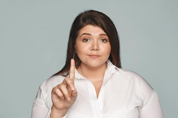 Non provarci nemmeno. bella giovane donna in sovrappeso sicura di sé con corpo sinuoso e capelli scuri che scuote il dito indice, facendo un gesto di rifiuto o di rifiuto, non interessata alla tua opinione. messa a fuoco selettiva Foto Gratuite