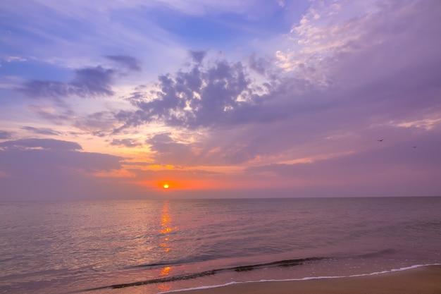 Вечер на пляже спокойного бескрайнего моря. разноцветный закат и облака Premium Фотографии