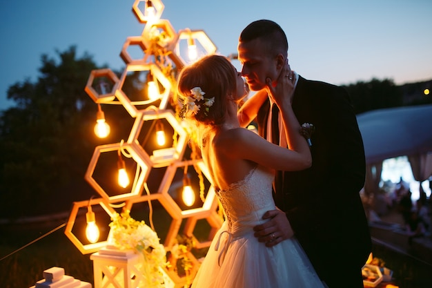Evening wedding ceremony. the bride and groom are on the background of the wedding arch. Premium Photo