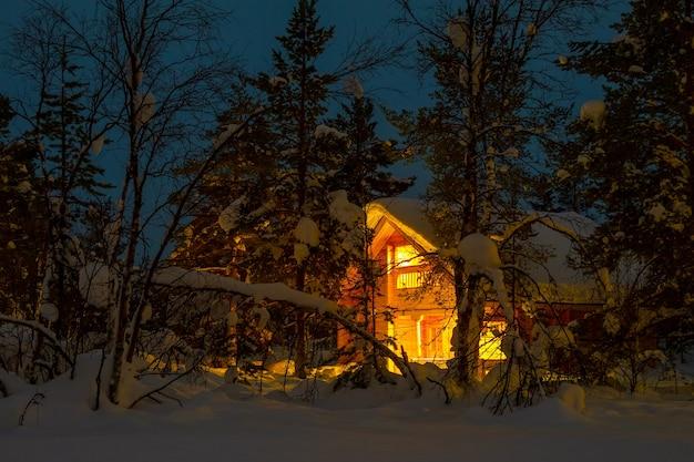 夕方の冬の森。大きな雪の帽子で覆われた枝。バックグラウンドで照明付きのコテージ Premium写真