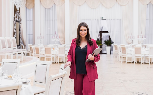 Event manager with laptop in banquet hall Free Photo