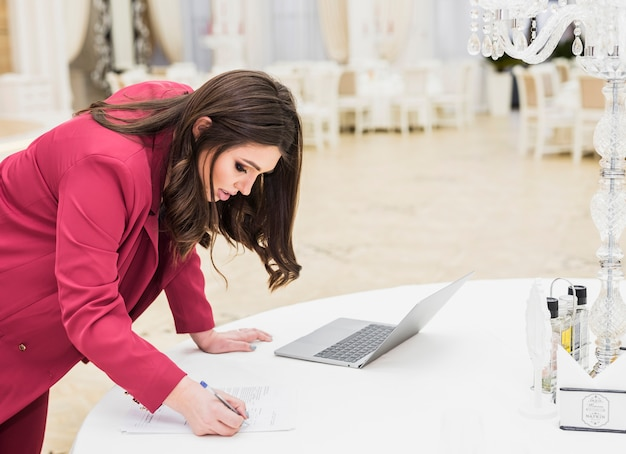 Event manager writing on paper in banquet hall Free Photo