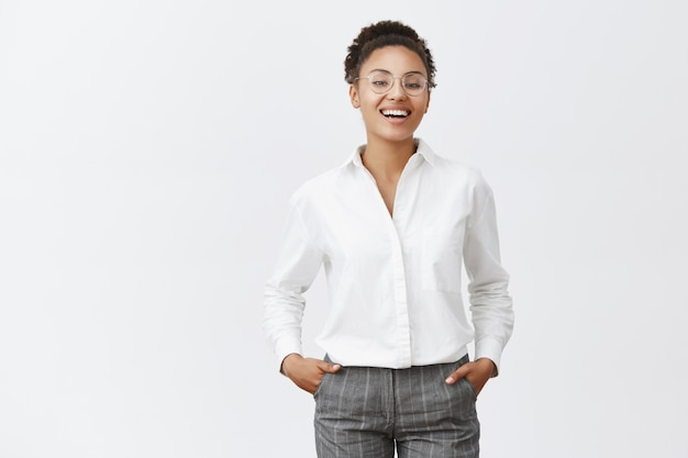 Everything under control. good-looking african female in glasses, shirt and pants, holding hands in pockets, smiling and laughing with confident expression, triumphing, seeing great results of work Free Photo