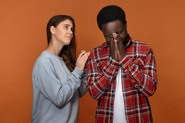 Andrà tutto bene. preoccupato amorevole giovane femmina caucasica sostenendo e rallegrando il suo marito afroamericano piangente depresso, esprimendo preoccupazione, tenendo la mano sulla spalla Foto Gratuite