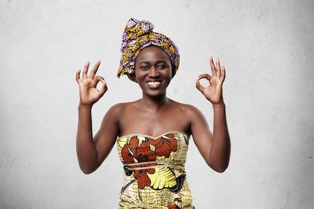 Va tutto bene! bella donna africana allegra che indossa sciarpa luminosa sulla testa e vestito elegante che mostra segno giusto che dimostra la sua soddisfazione e felicità concordando con qualcosa. Foto Gratuite