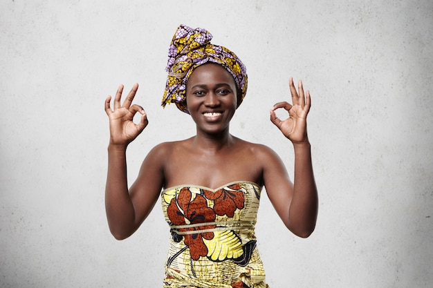 すべて順調です!頭に明るいスカーフを身に着けている美しい陽気なアフリカ女性と彼女の満足度と何かに同意する幸福を示すokサインを示すエレガントなドレス。 無料写真