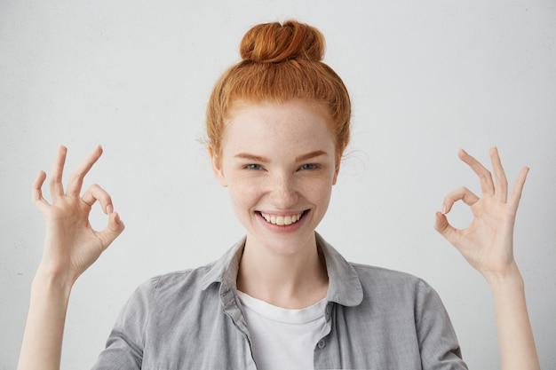 すべて順調です!生姜髪の結び目とそばかすのある肌で両手でokのジェスチャーを示し、広く笑って、彼女ののんきな幸せな生活を楽しんでいる陽気な興奮した若い白人女性 無料写真