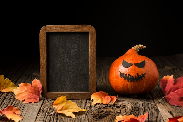 Evil halloween pumpkin surrounded by leaves Free Photo