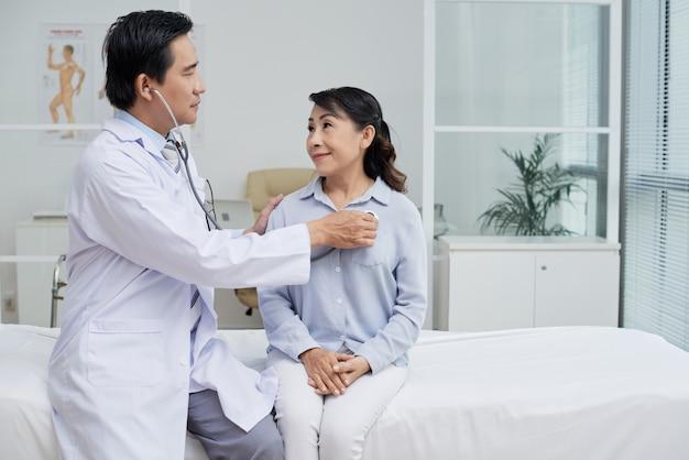 Examining senior patient with stethoscope Free Photo