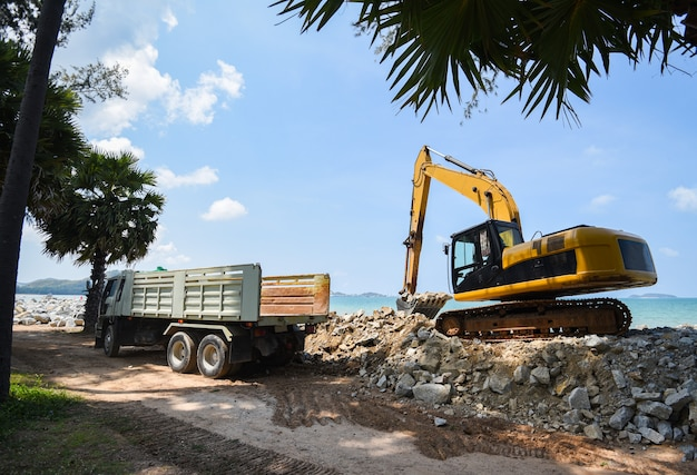 Excavator digger stone and dump truck working on construction site Premium Photo